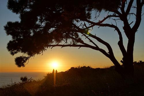 Zahlreiche Pilger erleben gemeinsam den makellosen Sonnenuntergang am Kap.