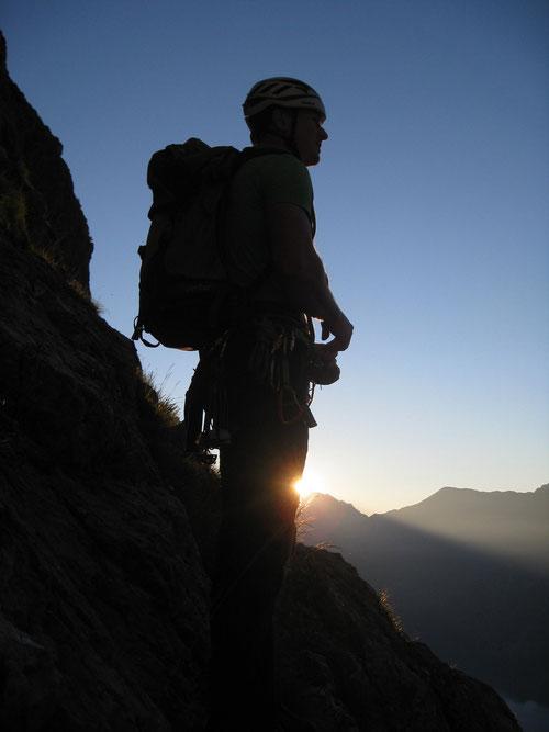 Die Sonne bricht über die Bergspitzen.