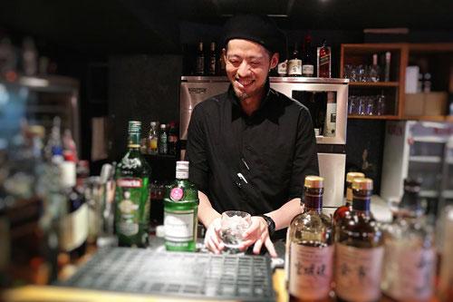 カウンターに立ち、グラスを用意する沓沢さん。少し照れているような笑顔。
