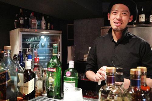 カウンターに立つ沓沢店長の写真。カウンターに並ぶ様々な酒瓶。