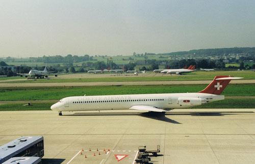 Neben der schönen MD-83 sei u.a. auch der Hintergrund erwähnt: Abgestellte Airbusse der gegroundeten Swissair!/Courtesy: Norbert Hahn