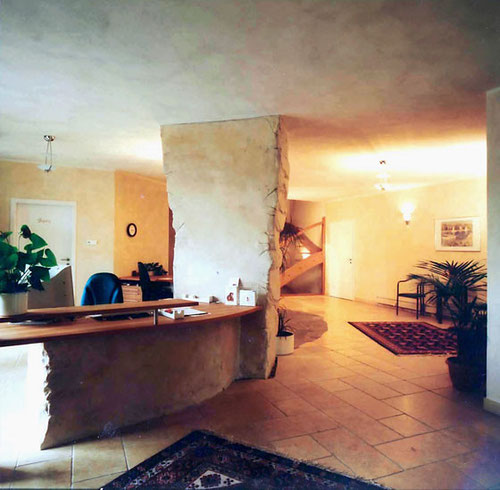 Lasierte Wände im Empfang einer Gemeinschaftspraxis Tresen mit mineralischen Materialien modelliert/ lasiert in Natursteinoptik.