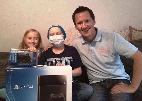 Lennard und seine Schwester Josephin freuen sich über die von DoppelPASSer Kim Häusgen überreichte PS4