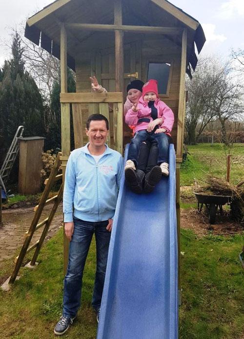 Lea und ihre Schwester freuen sich mit DoppelPASSer Kim über das Spielhaus im eigenen Garten