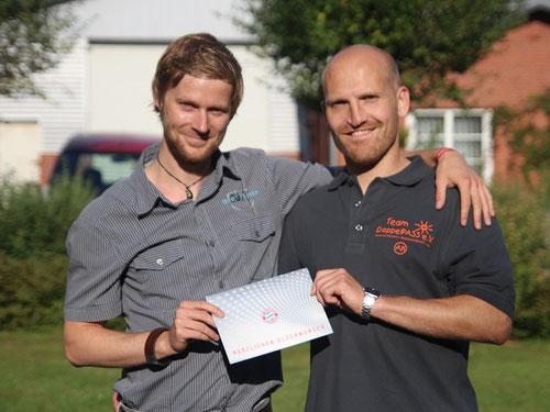 Steffen Ruwolt (SR20) nimmt seinen Gewinn von DoppelPASS-Tippspielleiter Alexander Klucke entgegen