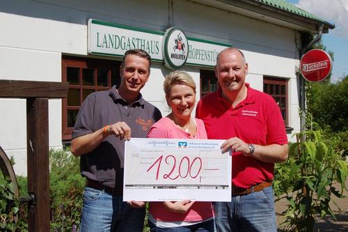 Torsten Schulz, Urte Scholler und Volker Scholler präsentieren den Spendenscheck über 1.200 Euro