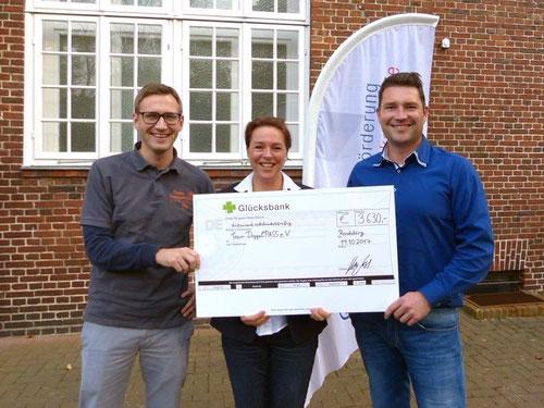 DoppelPASSer Eike nimmt den Scheck von Kai Lass, Geschäftsführer der WFG, und WFG-Mitarbeiterin Stephanie Greve in Empfang