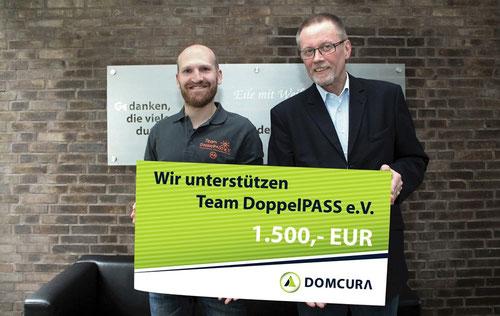Alexander Klucke nimmt die Spende von Manfred Lenzky von der DOMCURA AG symbolisch entgegen