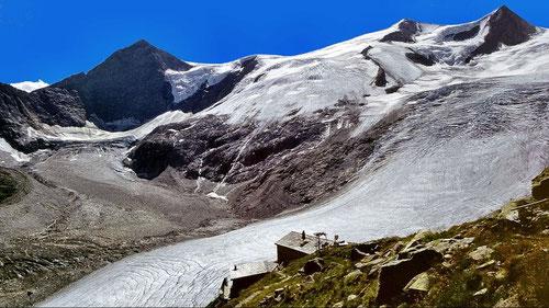 Hütte und Gletscher vor dunkler  spitziger Wand und blauem Himmel.