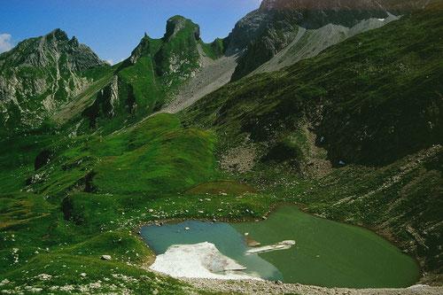 Kleiner Bergsee mit Lawinenresten und Eis unter dem steilen Abhang der Hochkünzelspitze