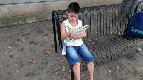 小学生もいっしょに朝学。ベンチに座って計算問題。