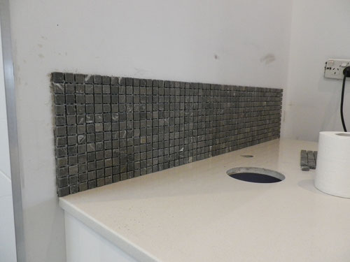 These tiles are grey, until they are grouted/get wet, and then they go brown. Re-did them with different grout but still brown