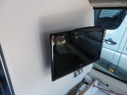 The TV is now mounted on the side of the fridge cupboard