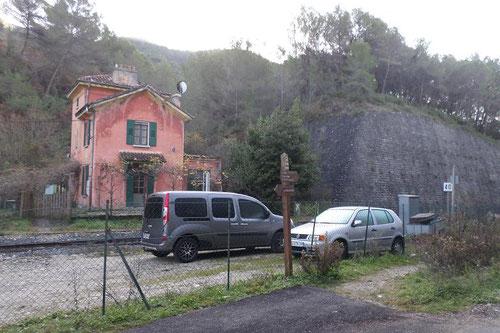 Maison rose devant laquelle se trouve le petit portillon pour traverser la voie férrée.