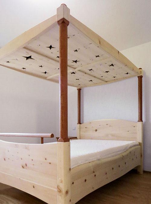 """Himmelbett """"Sterntaler"""": Zirbenbett mit Säulen und Fuß-Stange aus Elsbeere, Betthimmel mit ausgesägten Sternen"""