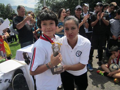 Juan Carlos Pinzón, recibe trofeo como el más destacado del 2012 en la categoría Sub-10, en compañía de Derly Castañeda, adminitradora de la Escuela de San Pablo-Bogotá.