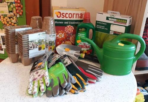 Gießkanne, Handschuhe, Gartenschaufel, Blumendünger, Gartenfleece, Anzuchttöpfe in zwei verschiedenen Formen