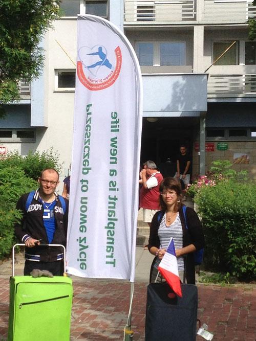 Greg et Elodie devant le drapeau des jeux