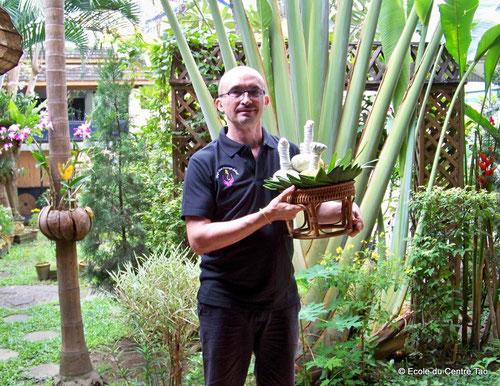 """Philippe Aspe à Chiang Mai montrant les pochons aux herbes médicinales ou """"compresses chaudes""""  utilisées dans le massage Chineitsang"""