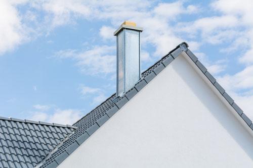 silberner Schornstein auf Dach vor blauem Himmel