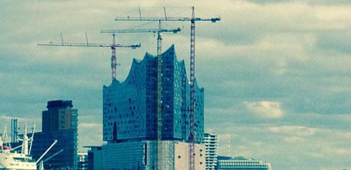 Projektmanagement-Training. Auf dem Bild sieht man die Baustelle der Elbphilharmonie in Hamburg. Es geht darum, durch gutes Training Projekte besser durchführen zu können.