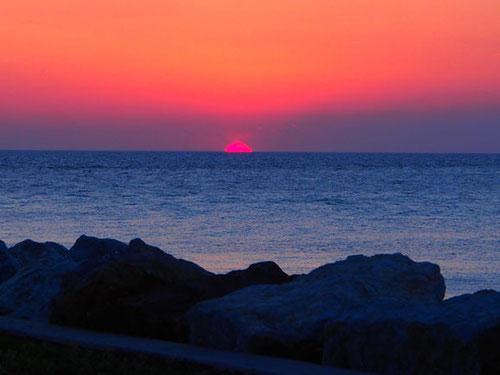 glutrot versinkt die Sonne im ligurischen Meer  zu Ende
