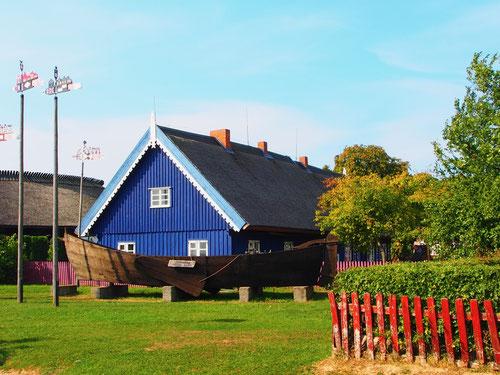 ein historisches Fischerhaus, mit den Mast-Wimpeln vor dem Haus