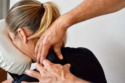 La photo représente un masseur qualifié qui procède au pétrissage du trapèze d'une salariée, lors d'un massage assis en entreprise.