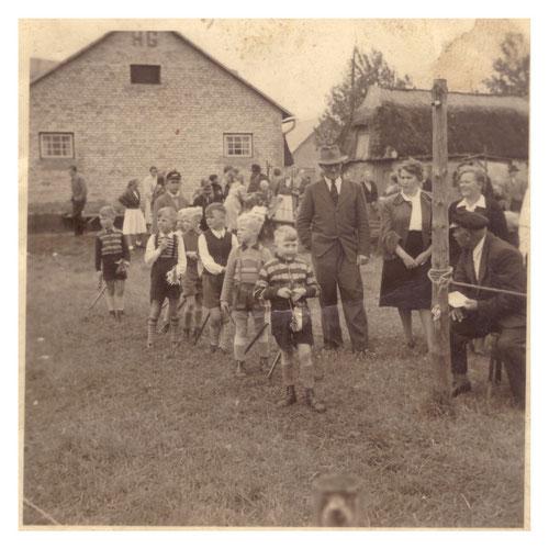 Dies ist ein Foto vom Kinderfest 1955. Im Wettkampf hatten die Jungen einen Holzstiel mit Pferdekopf (genannt Steckenpferd) und mussten, wie beim Ringreiten, einen Ring von einer Leine herunter holen. Das Kinderfest wird auch heute noch organisiert.