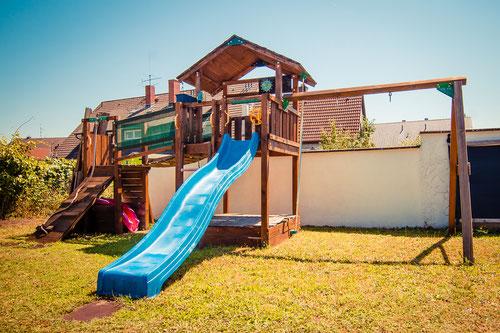 Im Garten haben wir ein großes Klettergerüst und einen Sandkasten und jede Menge Platz zum Toben.