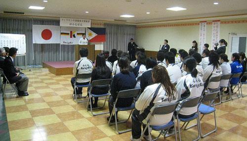 日本とフィリピンの国旗を前に神妙に「ご挨拶」を耳を傾けるフィリピン人