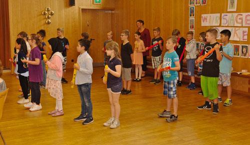 Die Kinder der Klasse 3c singen zu den Boomwhackers.
