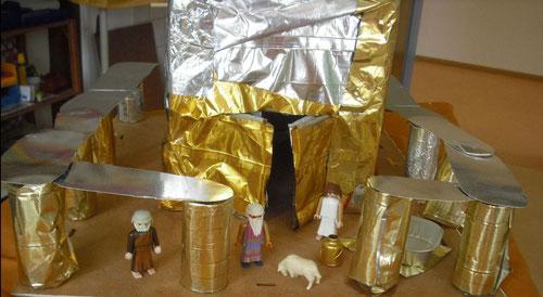 Unser Tempel aus einer Kiste, Klorollen, Schaumkusspackungen, Chipstüten, einem Katzenfutterschälchen und einer alten Fotorahmenrückseite.