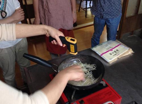温度を測りながらもやしを炒めています