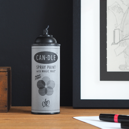 Ein Sprühdosen Kerze aus schwarzem Wachs steht auf einem Holzschreibtisch. Im Anschnitt eine gerahmte Skizze von Mode2 und ein pinker Layout-Marker liegt auf einem weißen Blatt Papier.