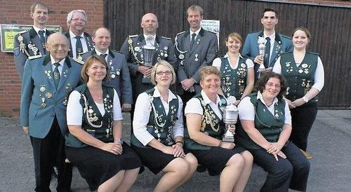 Harry Offermann (vorne li.) überreichte den Schützen vom Zollbaum, den Schützinnen vom Zollbaum und den Jungschützen vom Dobrock die Siegerpokale.