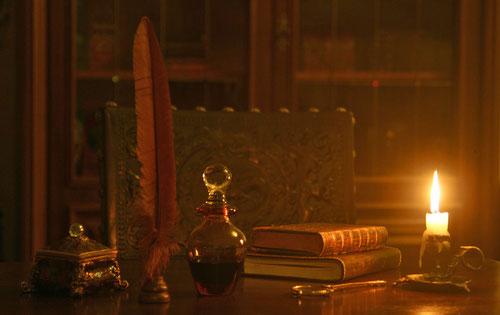 Fantasie und Wirklichkeit Fotografien und Gedichte Kathrin Steiger Schreibtisch mit einer Kerze zwei Büchern einer Schreibfeder einem Tintenglass