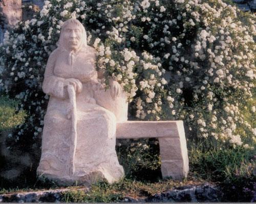 Steinplastik Frau sitzend auf Bank