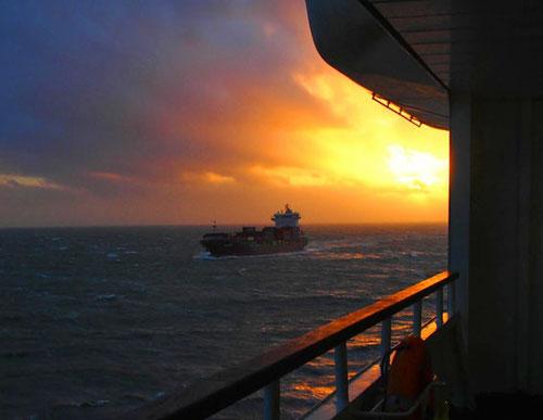 ein Frachter steuerbord voraus - der begleitende Sonnenuntergang gigantisch