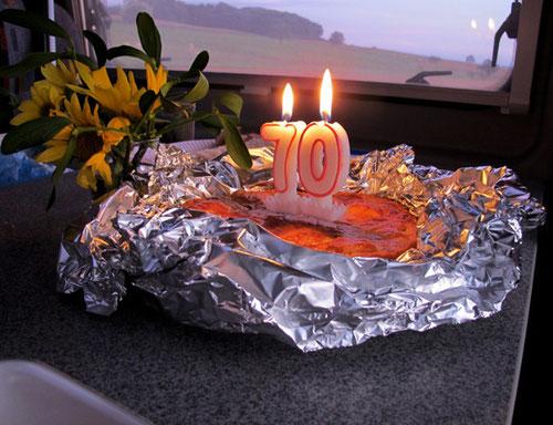 """der Geburtstagskuchen - mit einer """"leuchtenden 70"""" und einer freundlichen Sonnenblume - daneben"""