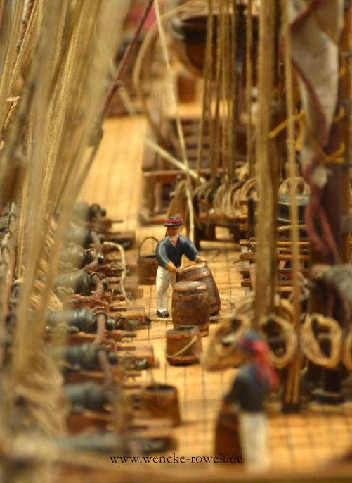 Kleine Figuren, Kanonen und Schießpulverfässer auf einem Modellschiff