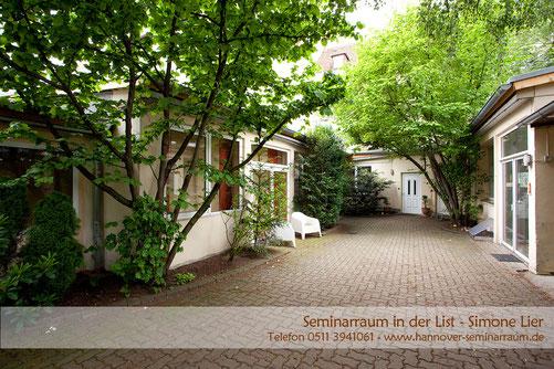 Well-balanced Institut von außen: ein niedriges Gebäude im Innenhof mit Stühlen inmitten von kleinen Bäumen