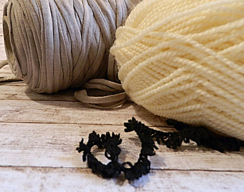 graues Textilgarn und weiße Wolle auf Holzboden