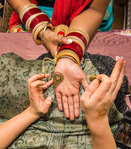 Indian bride being adorned with mehndi by travelling henna artist
