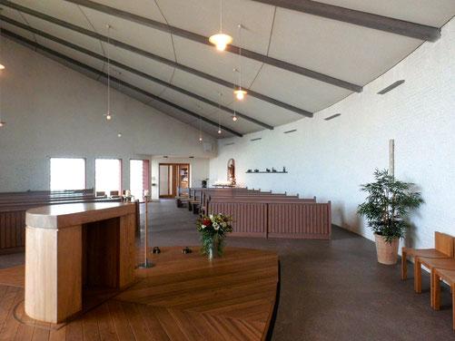 Innenansicht einer Kirche mit Holzaltar und Holzbänken