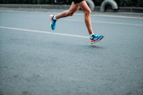 Man sieht die Beine eines Sportlers, der auf der Straße joggt.