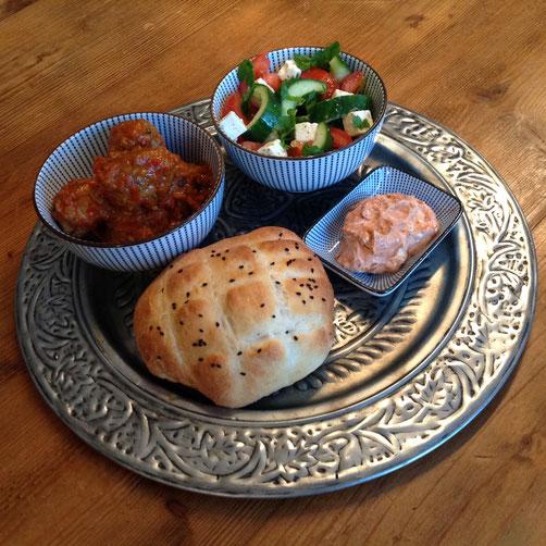 Turkse gehakballetjes in pittige geroosterde paprikasaus, met Turks brood, feta paprikadip en salade.