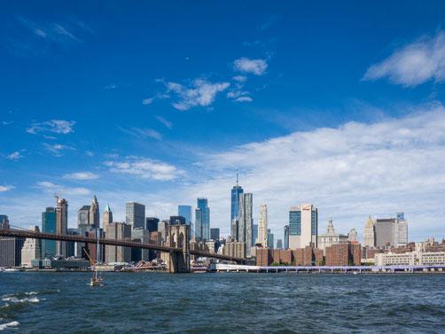 Der Blick vom East River auf Manhatten und die Brooklyn Bridge bei bestem Sommerwetter.