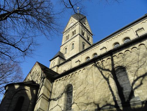 Hinter ein paar Baumästen ragt der neuromanische Kirchturm in den Himmel.