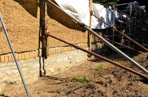 Gerichteter  Mauerteil mit Stahlstützen.  Im unteren Teil der neu gestaltete Wandfußpunkt und die Neuausrichtung des Natursteinsockels